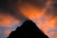 Fiery orange clouds hover above a mountain peak in North Cascades National Park, Washington.