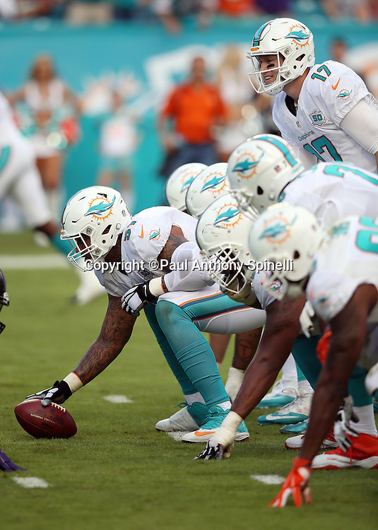 The Miami Dolphins offensive line gets set to snap the ball opposite the Baltimore Ravens defensive line at the line of scrimmage during the 2015 week 13 regular season NFL football game against the Baltimore Ravens on Sunday, Dec. 6, 2015 in Miami Gardens, Fla. The Dolphins won the game 15-13. (©Paul Anthony Spinelli)