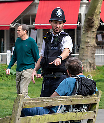 © Licensed to London News Pictures. 08/04/2020. London, UK. A policeman speaks to a man sitting on a bench at Barnes Pond. Police out in upmarket Barnes Village asking locals not to loiter in the warm weather with their lattes and picnics as Good Friday is set to be the warmest day of the year so far as the Coronavirus crisis continues. Photo credit: Alex Lentati/LNP