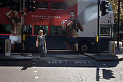 Lady is about to cross the road with macho men models in a Tommy Hilfiger bus ad behind in the City of London.