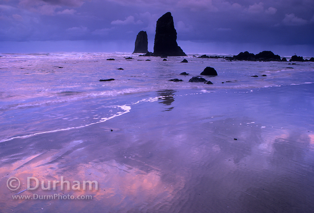 "A basalt rock formation on the Oregon Coast called ""needles"" at dusk with a rainstorm on the horizon. Cannon Beach, Oregon. 1998."
