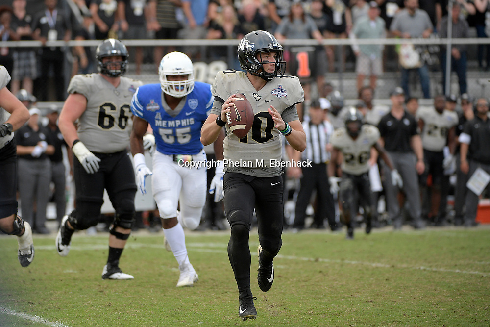 Central Florida quarterback McKenzie Milton (10) rolls out to throw a pass against  Memphis during the second half of the American Athletic Conference championship NCAA college football game Saturday, Dec. 2, 2017, in Orlando, Fla. Central Florida won 62-55. (Photo by Phelan M. Ebenhack)
