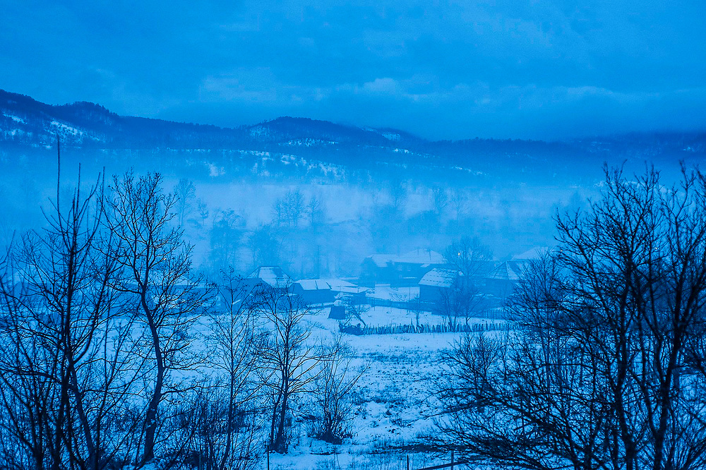 Romania: A view of the snow covered village of Botiza in the mist. Most young people from this village have gone to France to work.