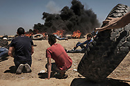 Palestinians gingerly move toward the outer fence with tires to be set ablaze a the Gaza-Israel border in Malaka during a mass demonstration against the opening of US embassy in Jerusalem, Gaza Strip on May 14, 2018. That day, more then 60 were killed by Israeli soldiers and over 1,400 we injured.