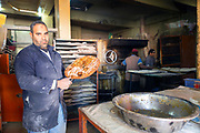 Madfouna is locally joked as being the Berber take on pizza in the southern Saharan regions and is even served to go in cardboard boxes from small take away stands in Rissani, Southern Morocco, 2017-12-16.<br /><br />It's not uncommon for these eateries to get so busy that people queue for more than an hour as the chefs rotate orders in the large fire ovens, which are also used to bake fresh bread and slow roast lamb, beef and whole chickens.<br /><br />Adjacent to the crumbling ruins of Sijilmasa, a medieval Saharan city that served as a trading stronghold along the caravan routes transporting goods to sub-Saharan Africa, the modern-day town of Rissani humbly stands as a gateway to the Erg Chebbi dunes.