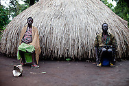 Congolese refugees sit outside their home in a refugee camp for people displaced by the LRA.