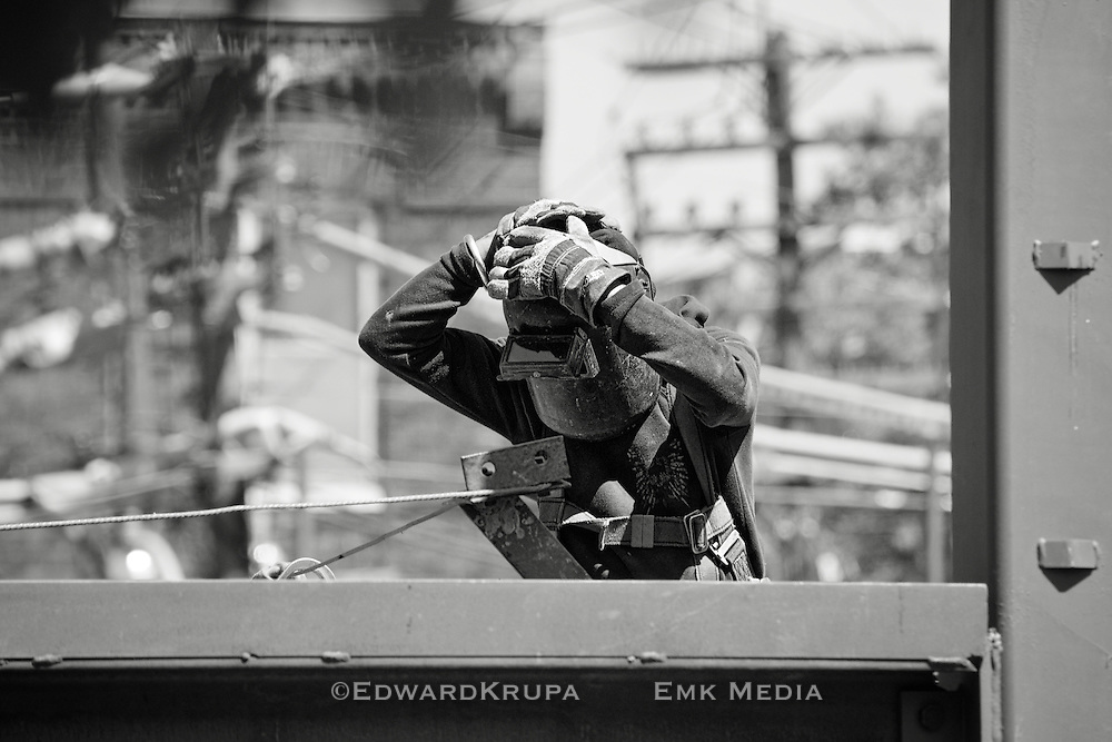 Iron worker putting welding mask on.
