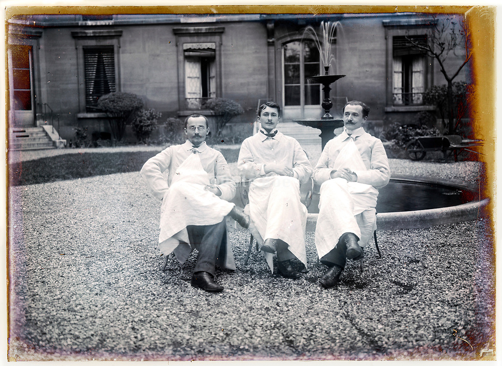 indoors servants wearing an apron sitting in a grand mansion courtyard early 1900s France