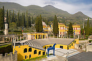 Amphitheatre, or Parlaggio, built 1931-52 and used for concerts, seating 1500, aerial view, at the home of Gabriele D'Annunzio, 1863-1938, Italian writer, soldier and fascist, at Vittoriale degli italiani, or The Shrine of Italian Victories, his estate and museums at Gardone Riviera, Lake Garda, Brescia, Lombardy, Italy. Blue Horse, by Mimmo Paladino, was installed here in 2010. The house or La Prioria, on the right, was originally the Villa Cargnacco, which was rebuilt by Gian Carlo Maroni from 1922 and developed until 1955. The estate consists of the Prioria, where d'Annunzio lived 1922-38, an amphitheatre, the protected cruiser Puglia, the MAS vessel used by D'Annunzio in 1918 and a mausoleum. It is part of the Grandi Giardini Italiani. Picture by Manuel Cohen