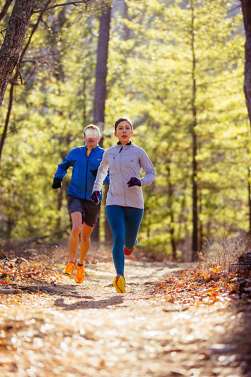 Man and woman winter trail running at Carvin's Cove outside Roanoke, Virginia, in the Blue Ridge Mountains.