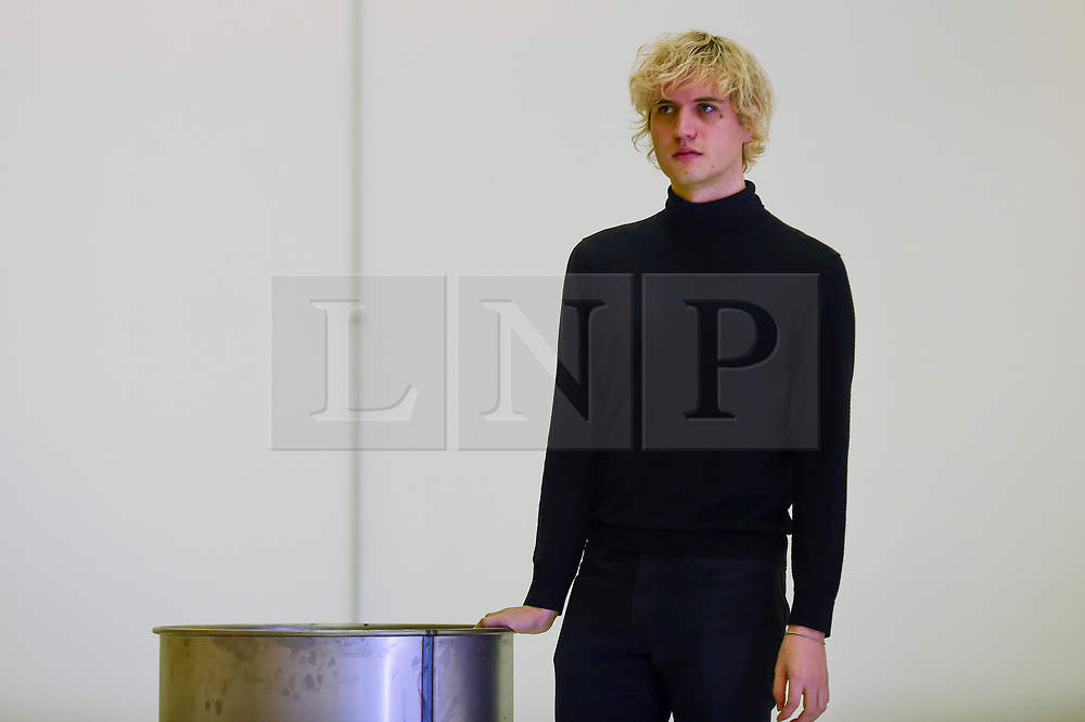 "© Licensed to London News Pictures. 07/11/2019. LONDON, UK.  British artist Patrick Staff poses with his work ""On Venus"", a site-specific exhibition commissioned by the Serpentine Sackler Gallery.  Altered lighting and reflective flooring combined with natural and synthetic liquids leaking from ceiling piping into steel barrels forms the major installation.   The exhibition, which also includes etchings and video work, runs 8 November to 9 February 2020.  Photo credit: Stephen Chung/LNP"