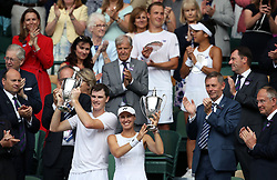 Martina Hingis and Jamie Murray celebrate victory in the mixed doubles final against Heather Watson and Henri Kontinen (back) on day thirteen of the Wimbledon Championships at The All England Lawn Tennis and Croquet Club, Wimbledon.
