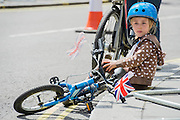 A girl waits with her mother for th rest of the family to catch up - Prudential RideLondon a festival of cycling, with more than 95,000 cyclists, including some of the world's top professionals, participating in five separate events over the weekend of 1-2 August.
