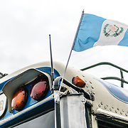 Guatemalan flag on a chicken buse behind the Mercado Municipal (town market) in Antigua, Guatemala. From this extensive central bus interchange the routes radiate out across Guatemala. Often brightly painted, the chicken buses are retrofitted American school buses and provide a cheap mode of transport throughout the country.