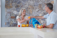 Husband handing wife orange from countertop
