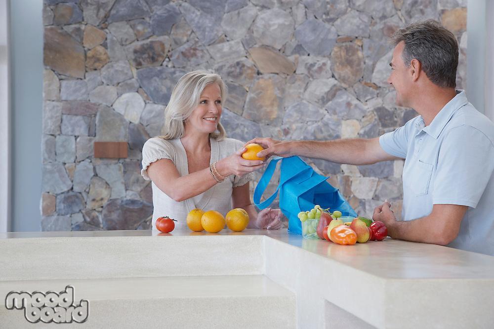 Husband handing wife orange from countertop