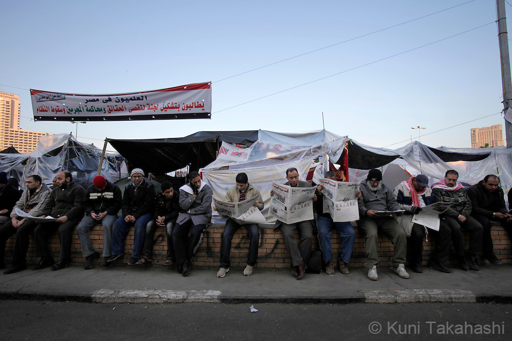 Anti-government protesters read newspaper at Tahir Square in Cairo Egypt on Feb 8, 2011- the 15th day of uprising demanding President Hosni Mubarak to step down. .Photo by Kuni Takahashi