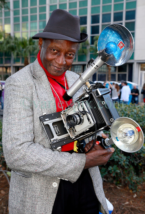 03 Feb 2013. New Orleans, Louisiana USA. .Super Bowl Sunday. Louis Mendes poses outside the entrance to the Superdome with his Speed Graphic. Mr Mendes makes his living selling polaroid portraits to game attendees.  The city hosts the XLVII (47th) Annual Super Bowl with the Baltimore Ravens against the San Francisco 49'ers. .Photo; Charlie Varley