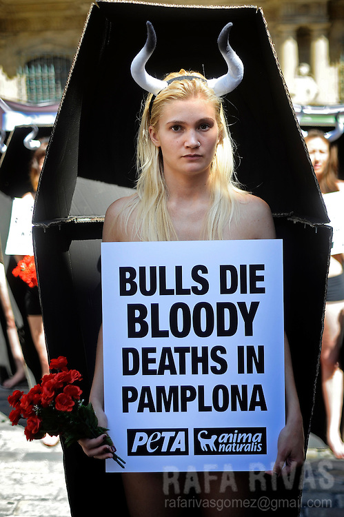 """Activists of PETA and Anima Naturalis pro-animal groups take part in an anti-bullfighting protest standing in coffins that represent the 48 bulls that will be killed during the San Fermin festivities in the Northern Spanish city of Pamplona. Posters read """"Bulls die a bloody death in Pamplona."""