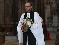 NEWS EDITORIAL USE ONLY. NO COMMERCIAL USE. NO MERCHANDISING, ADVERTISING, SOUVENIRS, MEMORABILIA or COLOURABLY SIMILAR. Reverend Anthony Ball, Canon of Westminster in Westminster Abbey in London with Princess Beatrice's wedding bouquet which, like those of Royal brides, is traditionally placed on the Tomb of the Unknown Warrior.