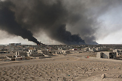 Licensed to London News Pictures. 02/11/2016. Qayyarah, Iraq. Smoke from burning oil wells, set alight by retreating Islamic State militants, are seen from the vandalised Qayyarah Cemetery (foreground) in Qayyarah, Iraq. Headstones in the cemetery were smashed by ISIS extremists who believe that a grave should be flat to the earth and without markings, during the towns two year ISIS occupation.<br /> <br /> Two months after being liberated from the Islamic State, the Iraqi town of Qayyarah, located around 30km south of Mosul, is still dealing with the environmental repercussions of their ISIS occupation. The town's estimated 15,000 inhabitants constantly live under, and in, heavy clouds of smoke which often envelope the settlement. The clouds emanate from burning oil wells in a nearby oil field that were set alight by retreating ISIS extremists after a two year occupation. The proximity of the fires, often right next to homes within the town, covers many buildings and residents with thick soot and will lead to long term health and environmental implications. Photo credit: Matt Cetti-Roberts/LNP