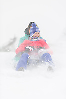 Cheerful young couple sledding in snow