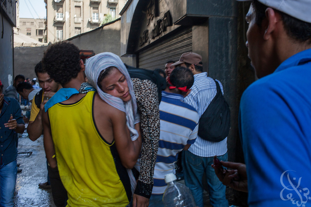 "Supporters of deposed Egyptian President Mohamed Morsi evacuate a female protestor overcome by tear gas near the frontline of intense street clashes around Ramsis Square during the August 16, 2014 ""Day of Rage"" protests in Cairo, Egypt."