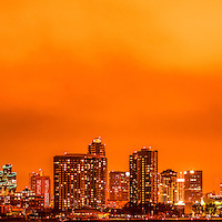 San Diego panoramic picture of the San Diego skyline at night with orange tone. Panoramic picture ratio is 1:3. San Diego is a major city in Southern California in the United States.