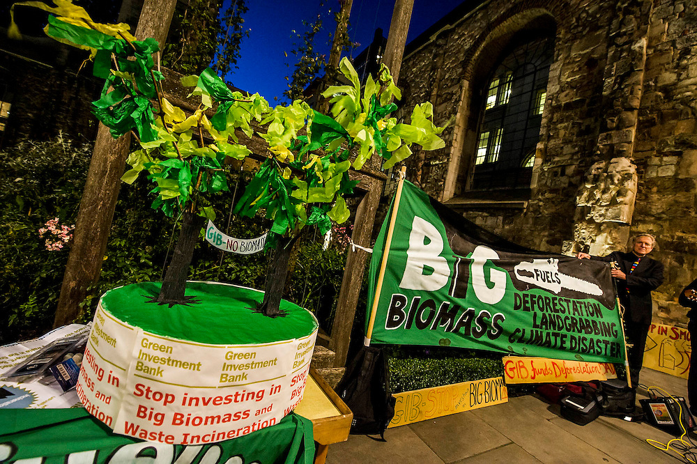 Environmental campaigners protest outside the 2nd anniversary investor meeting of the Green Investment Bank.  They are concerned about its support for the use of biomass as a fuel in power stations because it is from unsustainable sources. The meeting takes palce at the the offices of Bank of America Merrill Lynch, St Pauls, London 28 Oct 2014.