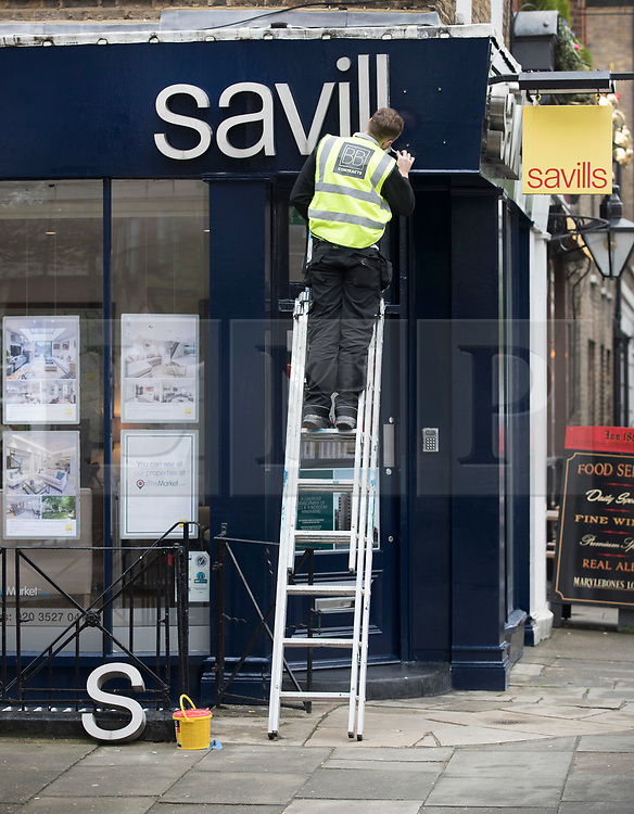 © Licensed to London News Pictures. 10/04/2018. London, UK. A workman mends a sign at Savills estate agents in central London. Photo credit: Peter Macdiarmid/LNP