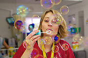 Senior Health Play Specialist, Jennifer Grange,  blowing bubbles for a child on the ward.