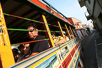 """Tourists ride in a """"Chiva"""" an open air old-style bus, through the streets of the """"Old City"""" in Cartagena, a unique travel destination on Colombia's Caribbean coast. (Photo/Scott Dalton)"""