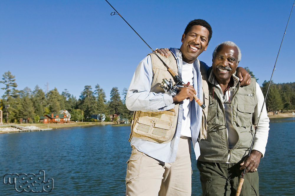 Senior man and son holding fishing rods by lake smiling (portrait)