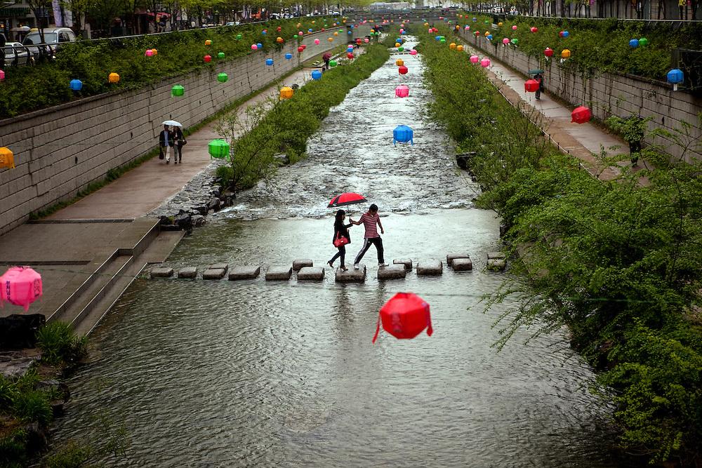 Der Cheonggyechon wurde in den 60er Jahren durch eine mehrspurige Strasse verdeckt. Inzwischen hat jedoch auch die Stadt Seoul den Wert von Gr&cedil;nfl&permil;chen erkannt und in einem aufwendigen Projekt die (ohnehin mit Sicherheitsm&permil;ngeln behaftete) Strasse wieder entfernt. Entstanden ist ein neuer, nun allerdings k&cedil;nstlicher Fluss quer durch das Zentrum der Stadt, dessen Wege zu einem Spaziergang einladen. F&cedil;r die Feierlichkeiten von Buddhas Geburtstag (2. Mai diesen Jahres) wurde der Bereich mit bunten Lampions dekoriert.<br /> <br /> Cheonggyecheon is a nearly 6 km long, modern public recreation space in downtown Seoul, South Korea. The massive urban renewal project is on the site of a stream that flowed before the rapid post-war economic development required it to be covered by transportation infrastructure. The $900 million project attracted much criticism initially but opened in 2005 and is now popular among Seoul residents and tourists. For the celebration of Buddhas birthday (2nd of May this year) the area was decorated with colorful lampions.