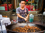 "18 MAY 2017 - BANGKOK, THAILAND: A man roasts chestnuts on Yaowarat Road in Bangkok. City officials in Bangkok have taken steps to rein in street food vendors. The steps were originally reported as a ""ban"" on street food, but after an uproar in local and international news outlets, city officials said street food vendors wouldn't be banned but would be regulated, undergo health inspections and be restricted to certain hours on major streets. On Yaowarat Road, in the heart of Bangkok's touristy Chinatown, the city has closed some traffic lanes to facilitate the vendors. But in other parts of the city, the vendors have been moved off of major streets and sidewalks.      PHOTO BY JACK KURTZ"