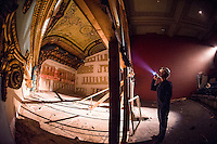 Superintendant Bob Ferguson from Bonnette, Page and Stone shines his flashlight to into the upper balcony stage area of the Colonial Theater in downtown Laconia.  (Karen Bobotas/for the Laconia Daily Sun)
