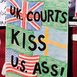 LONDON, UK - 30th May 2012: a banner reads 'U.K. courts kiss u.s. ass' outside the Supreme Court in central London, minutes after Assange's loss of his extradition appeal.