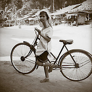A girl from the Long Neck tribe pauses for a portrait with bicycle. The tribe from Burma are living in refugee camps in Western Thailand.