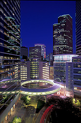 Downtown Houston, Texas cityscape at night with circular skywalk connecting buildings.