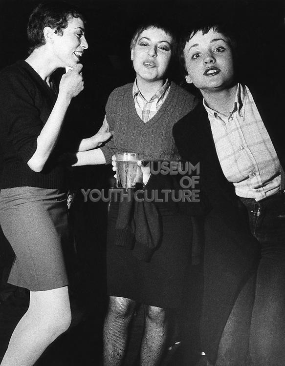 Three skinhead / mod girls, women, laughing and drinking, UK, 1980's