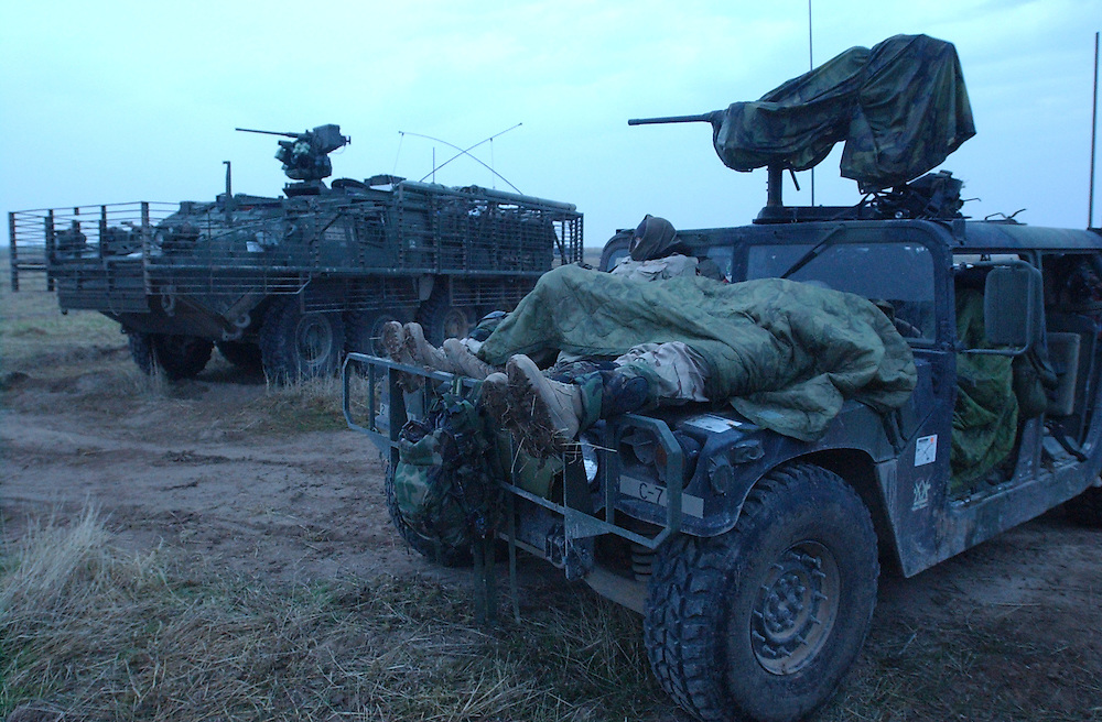 Soldiers from 5th Battalion, 20th Infantry Regiment, 3rd Brigade, 2nd ID, try to get some rest on top of their Humvee while taking a break from patroling near Samara, about 60 miles north of Baghdad early Monday morning. (Alan Lessig/Army Times)