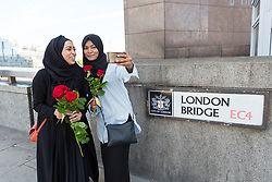 """© Licensed to London News Pictures. 11/06/2017. LONDON, UK.  Two women take a selfie with red roses on London Bridge this afternoon. 1,000 red roses with messages of """"love and solidarity"""" were given to passers by on London Bridge today.  Photo credit: Vickie Flores/LNP"""