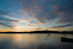 Sunset over the calm waters and moored boats at Three Mile Harbor on Long Island, New York