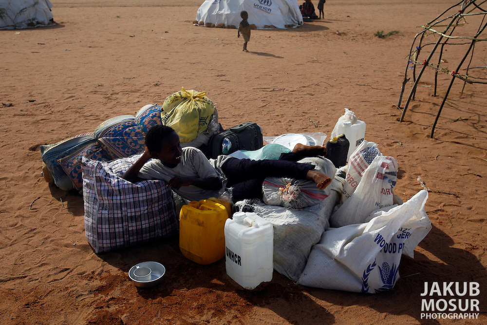 September 14, 2006 - A Somali child lays on his family's possessions while his home is constructed at the Dagahaley Refugee Camp in Dadaab, Kenya, 50 miles from the Somali border. Somalis are fleeing from recent clashes between Somalia Union of Islamic Courts and Somali warlords. Over 21,000 refugees since January 2006 have arrived in Dadaab which has a growing population of 140,000 refugees, in the North Eastern province of Kenya..(Photo by Jakub Mosur/Polaris)