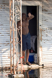 05 Sept  2005. New Orleans, Louisiana. Post hurricane Katrina.<br /> Residents who refuse to leave. Leaning from his front door above the water level, Rogers Jefferson, a resident of Uptown New Orleans refuses to leave the devastated flood areas.<br /> Photo; ©Charlie Varley/varleypix.com