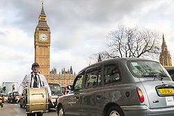 Whitehall, London, February 10th 2016. A taxi driver beats a funeral drum as an estimated 8,000 cabbies hold a go-slow in protest against what they say is unfair competition from minicab and Uber drivers who do not have to undergo the rigorous training and checks required for the licenced taxi trade. ///FOR LICENCING CONTACT: paul@pauldaveycreative.co.uk TEL:+44 (0) 7966 016 296 or +44 (0) 20 8969 6875. ©2015 Paul R Davey. All rights reserved.