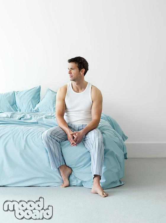 Man in nightwear sitting on bed