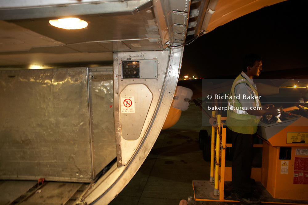 A cargo handler operates a loader to place freight containers into the hold of a Sri Lankan Airlines Airbus A340 at Male.