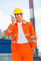 Happy architect wearing reflective workwear communicating on walkie-talkie at site