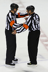 Dec 1, 2011; San Jose, CA, USA; NHL referee Chris Rooney (5) and referee Brian Pochmara (16) discuss a call during the third period between the San Jose Sharks and the Montreal Canadiens at HP Pavilion.  San Jose defeated Montreal 4-3 in shootouts. Mandatory Credit: Jason O. Watson-US PRESSWIRE